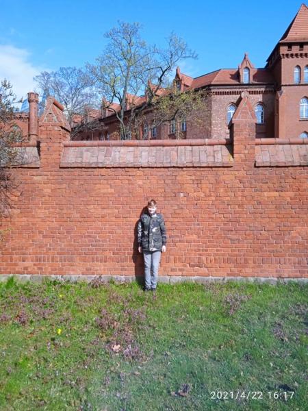 Junge vor einer Ziegelmauer