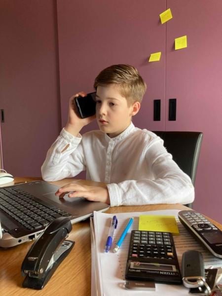 Junge mit Handy am Schreibtisch