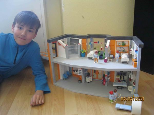 Junge vor Playmobilkrankenhaus