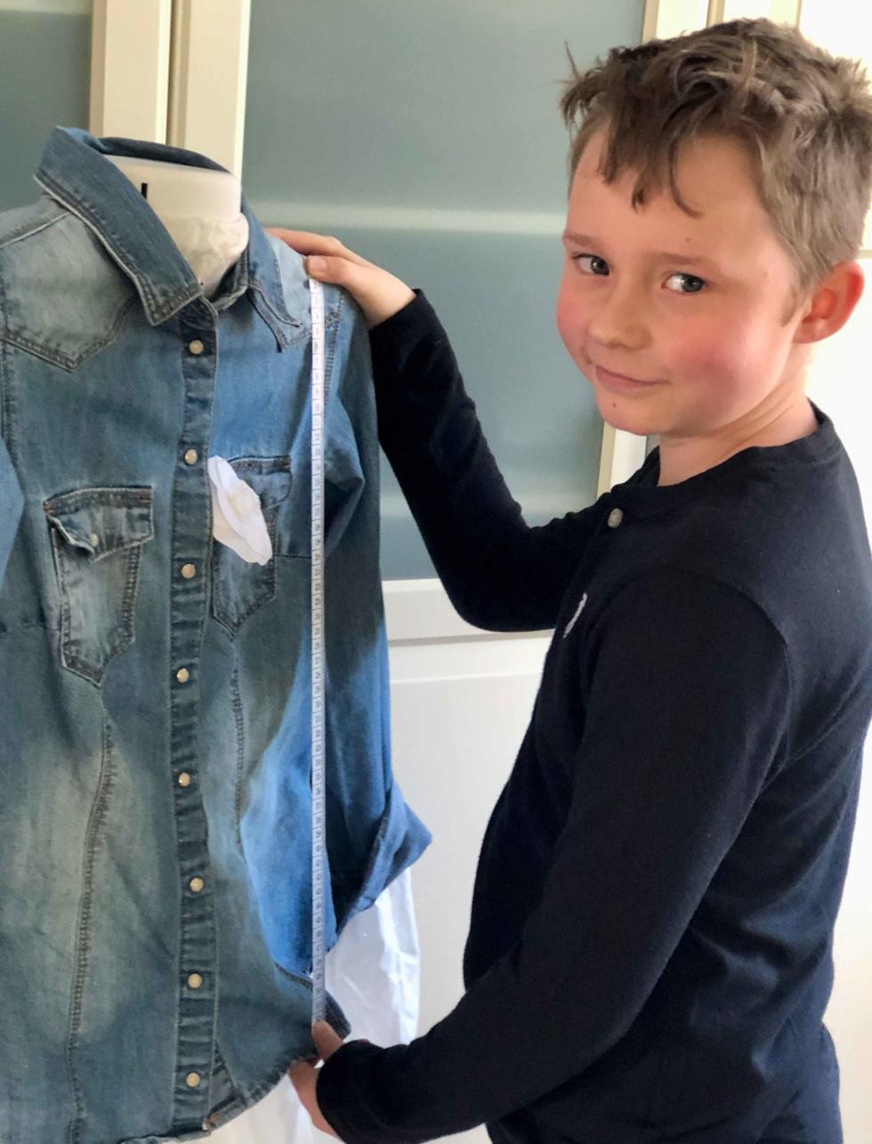 Junge mit Maßband an einem Jeanshemd