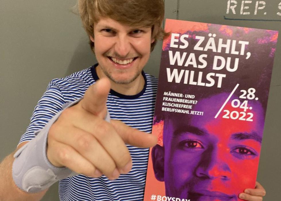 Junger Mann zeigt in die Kamera und hält Plakat vom Boys'Day