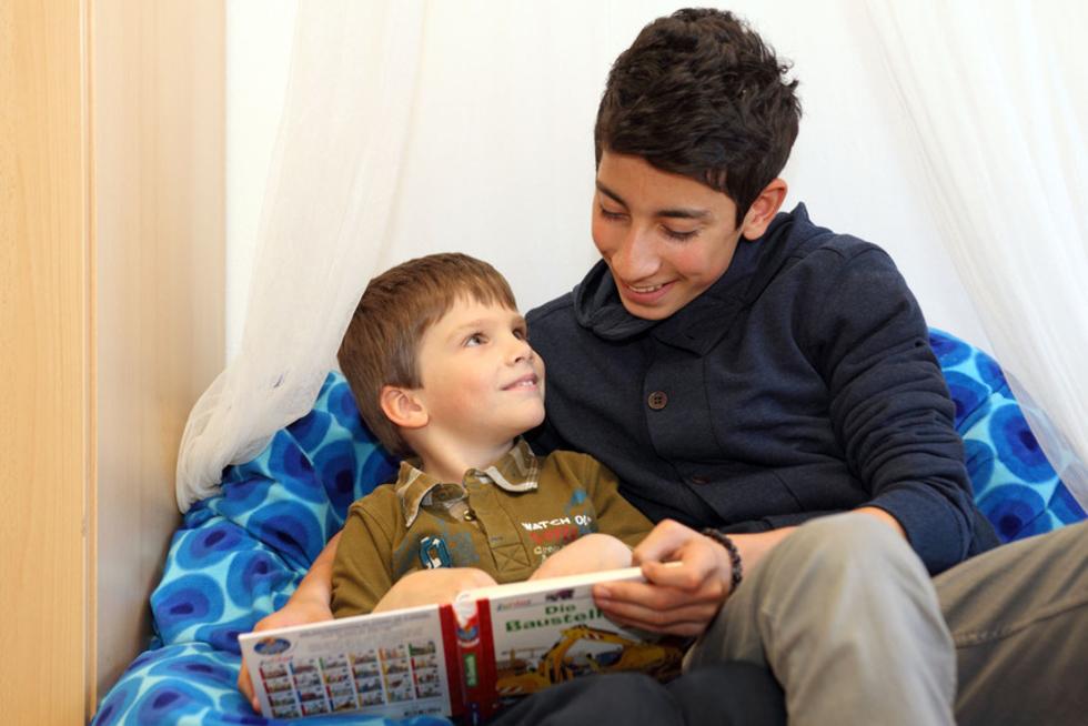Junge liest Kind vor