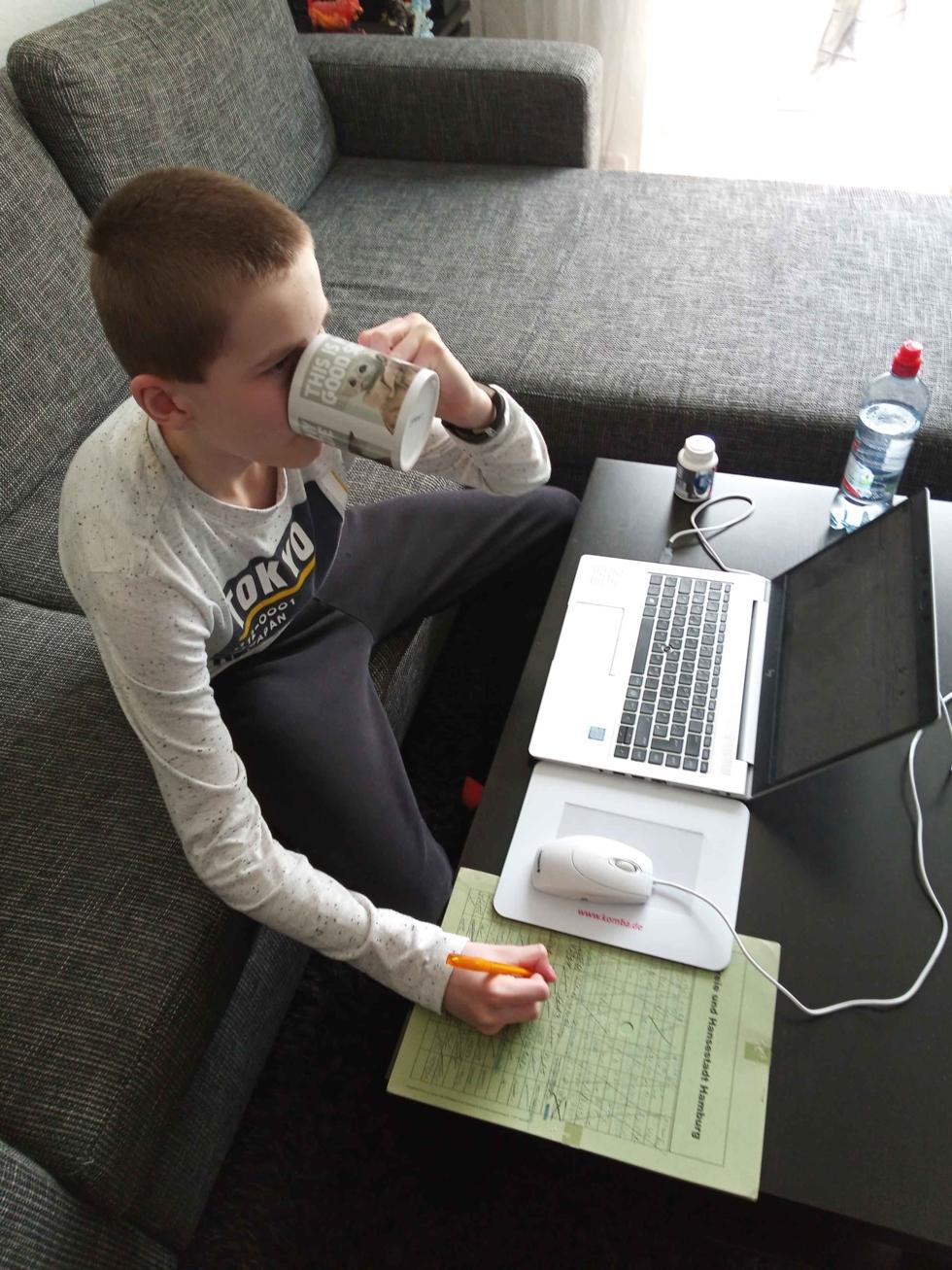 Junge mit Kaffetasse und Laptop auf dem Sofa