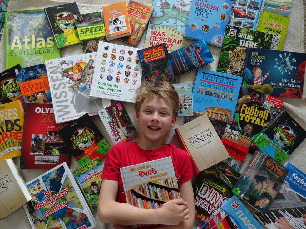 Junge mit vielen Büchern um sich herum