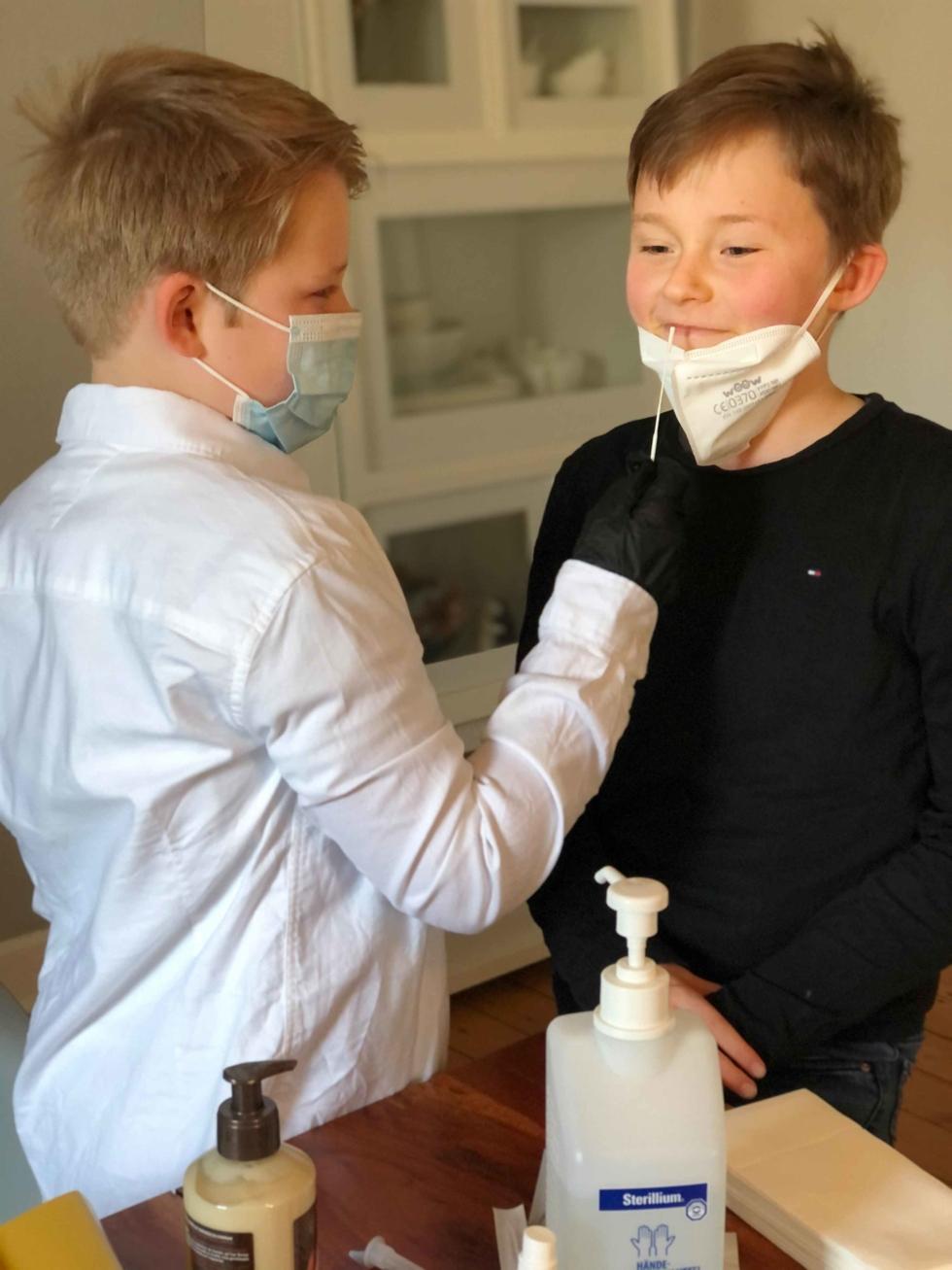 Jungen mit Masken und Coronatests
